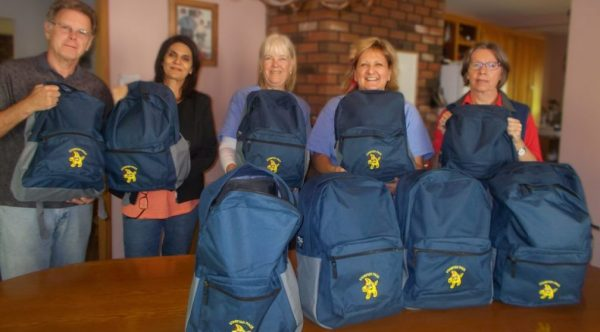 A team of people display their Starfish backpacks.
