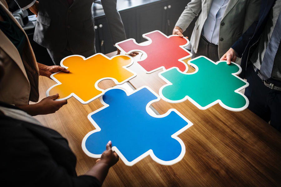A small team of people hold their puzzle pieces together to see if they fit.