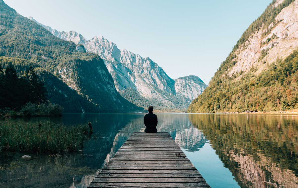 A person sits on a dock looking out over the water and the mountains beyond.