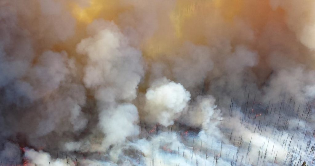 The smoke coming off of a forest fire billows as seen from above, in the glow of the fire.