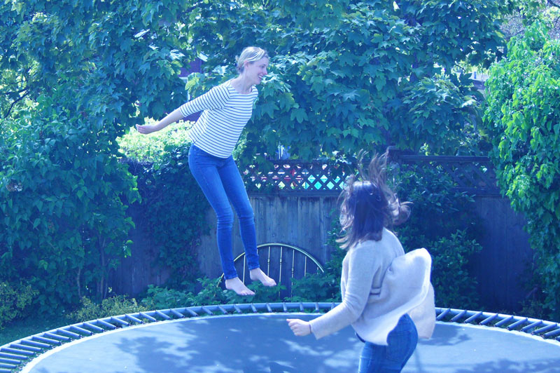 Kerri jumps on a trampoline with someone else.