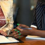 The hands of two colleagues in a meeting at work. The person on the left has long gold nails. The person on the right has long green nails. The person on the left is resting her left hand on a folder with lines paper in it. They are working on a shiny wooden table.
