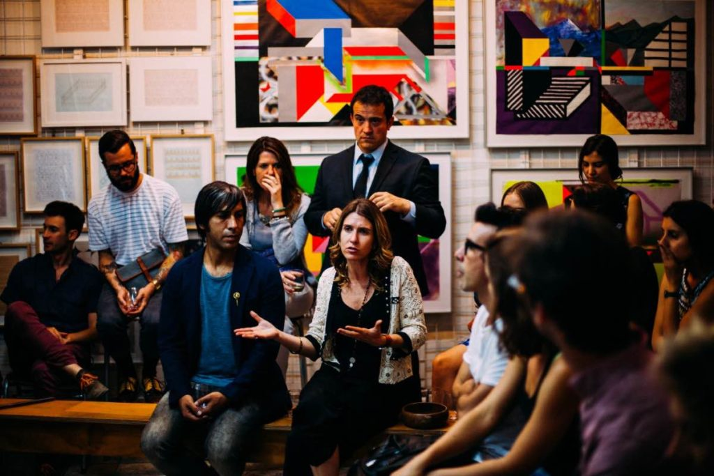 A group of people in a U shape in an office with abstract art on the wall. Most people are focussed on a femme presenting person in the centre of the room speaking with their hands.