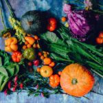 Pumpkins, squash, spinach, an onion, and a variety of other veggies on a blue countertop.