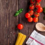 Uncooked pasta, a wooden spoon, a dish towel, tomatoes, and basil leaves spread out on a dark wooden table.