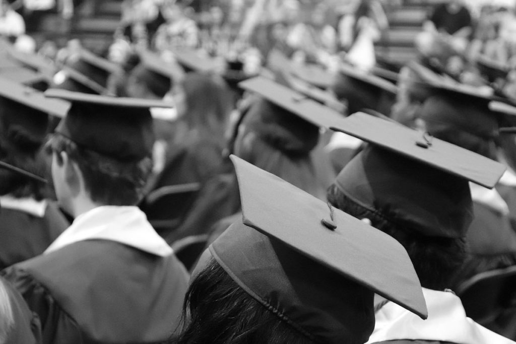 A black and white photo of a crown of people with graduation caps on. They are all facing away from the camera.