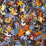A heap of multicoloured, unsorted puzzle pieces.