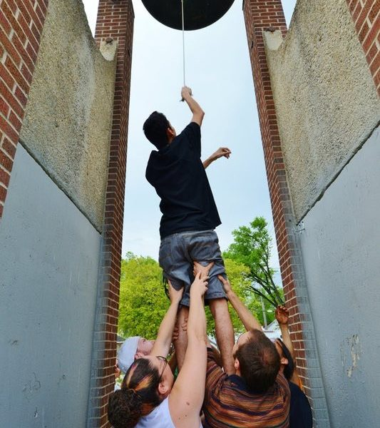 Three people face away from the camera and are reaching up to hold a man's legs as he balances on their shoulders to reach a bell hung high between two brick and concrete buildings.