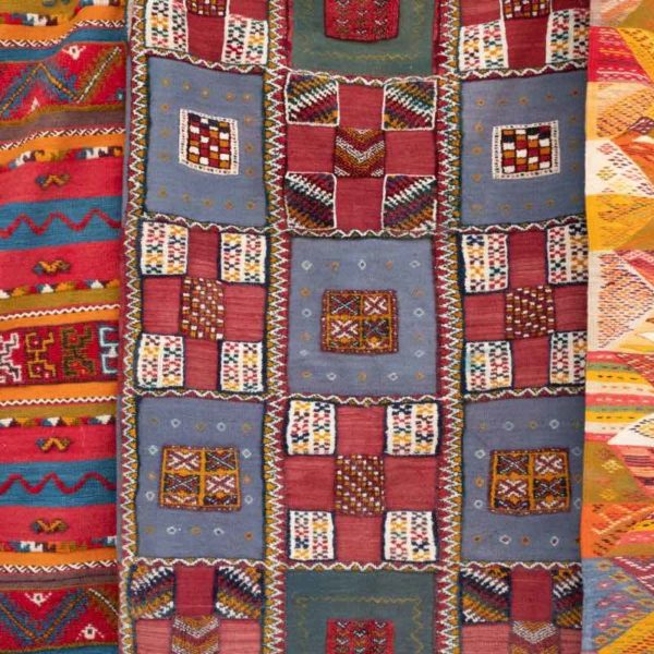 A red, orange, blue, and green patch work quilt.