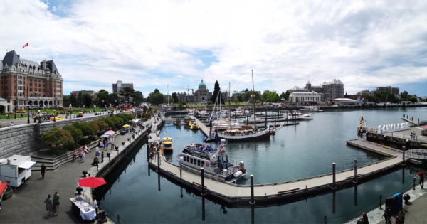 Victoria harbour with docks, walkways, water taxis, and people milling about.