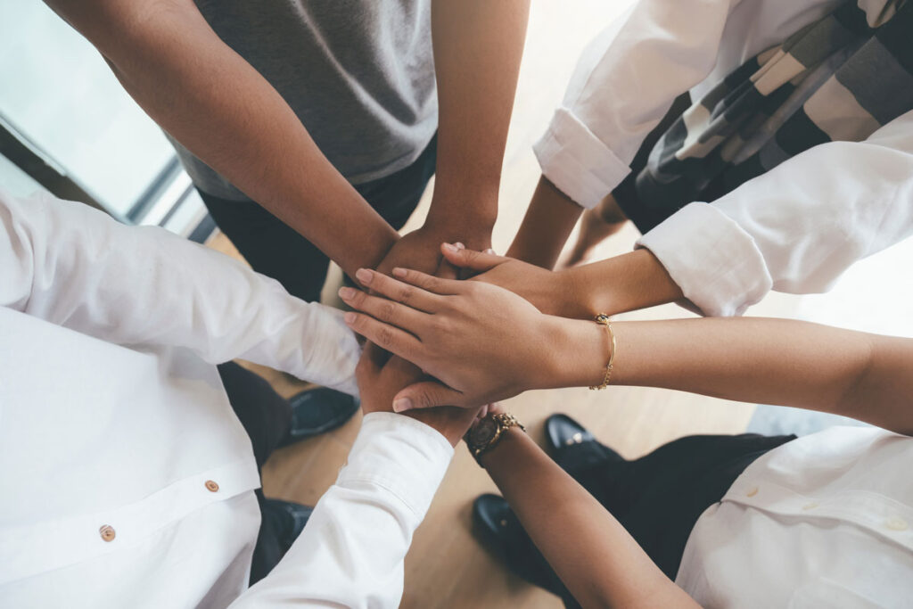 A group of people stand in a circle and put their hands over each other.