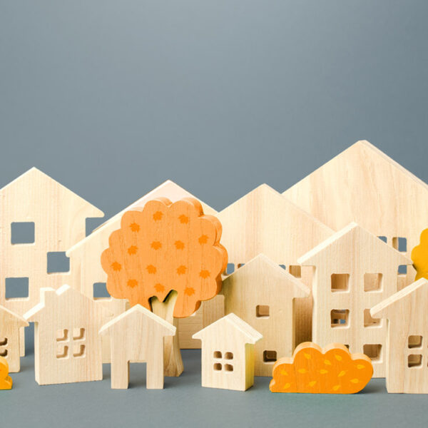 Many tiny wood houses and sheds and wooden tree models site on a grey background.