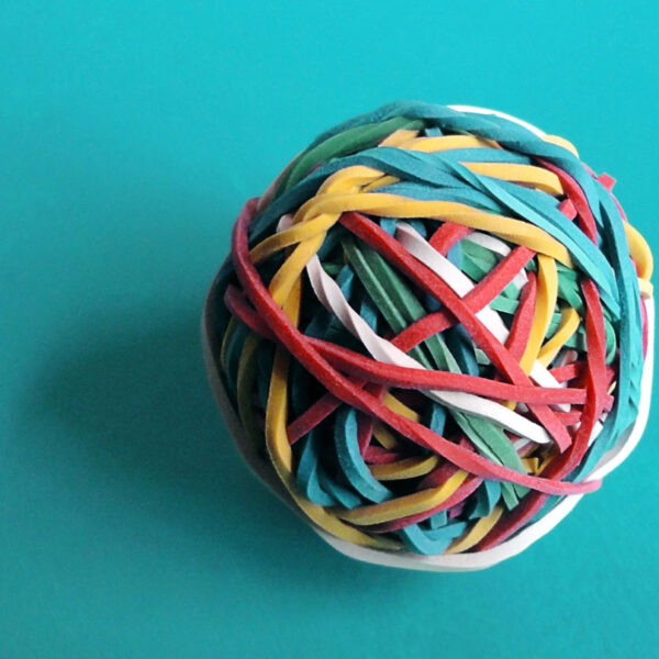 A ball of rubber bands stands on a turquoise table.