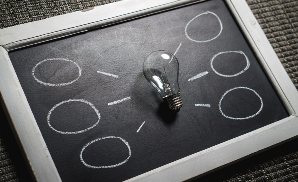A lightbulb stands in the middle of three chalk circles.