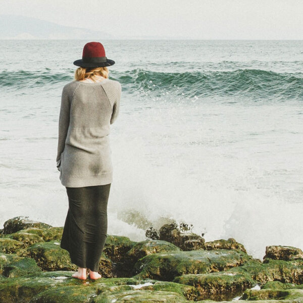 A woman stands on a dock looking out at the grey ocean water in the wind.